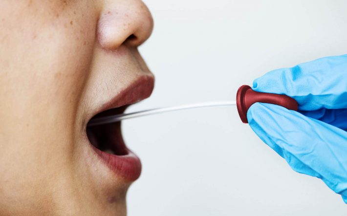 Woman getting a mouth swab to test for coronavirus